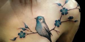 Ave sobre rama de flores azules