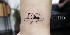 Oso panda durmiendo sobre caña de bambú