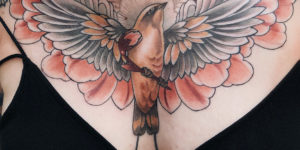 Ave de alas abiertas con flores por Jen Tonic
