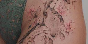 Avecilla apoyada sobre una rama de flores de cerezos