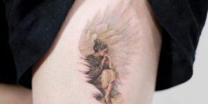 Mujer acurrucada en las alas de un ángel