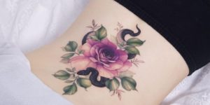 Serpiente asomada entre flor rosa por Tattooist Silo