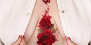 Flores rosas desvaneciéndose en Mariposa por Peria Tattoo