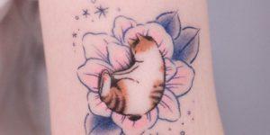 Gatito tomando una siesta sobre la flor por Minari Tattoo